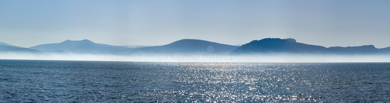 与低雾云彩的海景在海水在与太阳光的清早 库存照片