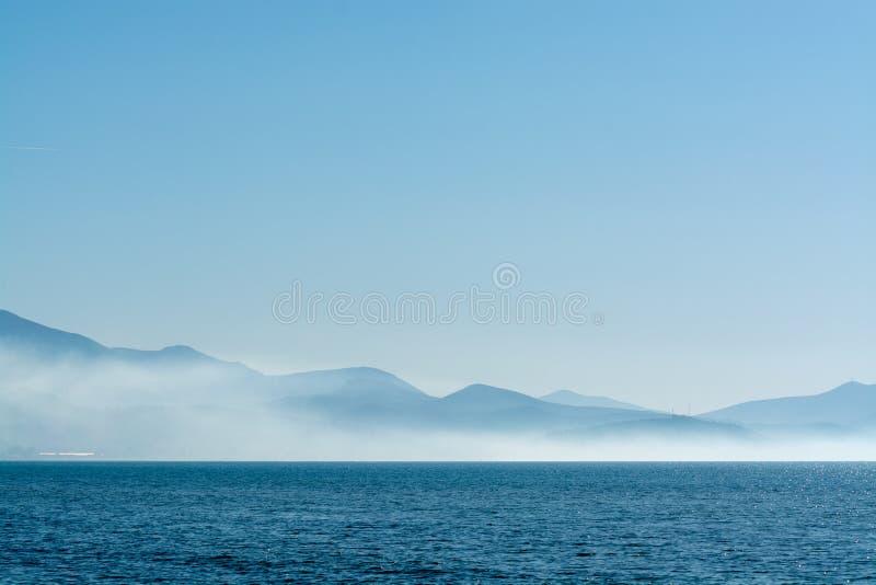 与低雾云彩的海景在海水在与太阳光的清早 免版税库存照片