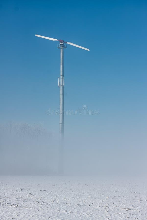 与低雾和风轮机的荷兰冬天风景 库存照片