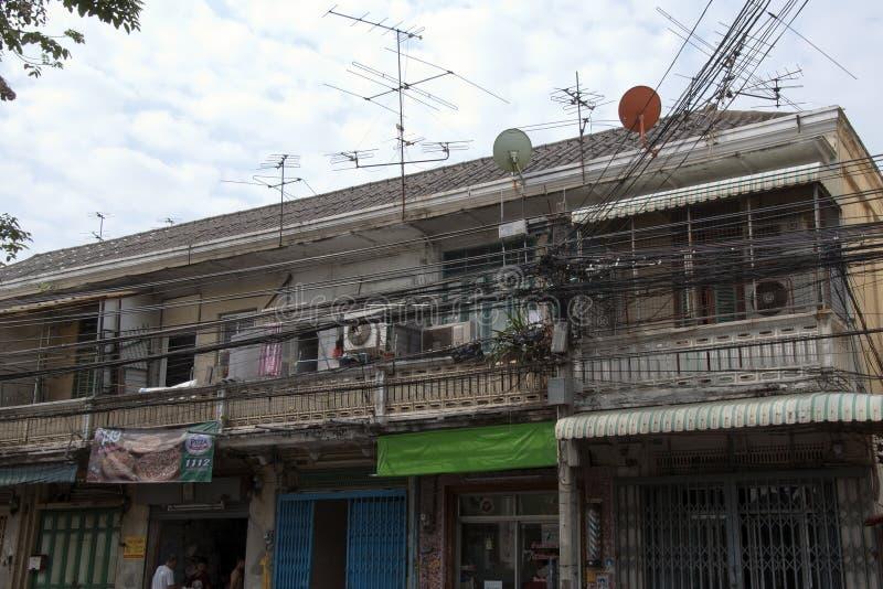 与住房、商店和现代技术的典型的住宅街道场面包括电源杆,缚住和卫星盘 库存照片