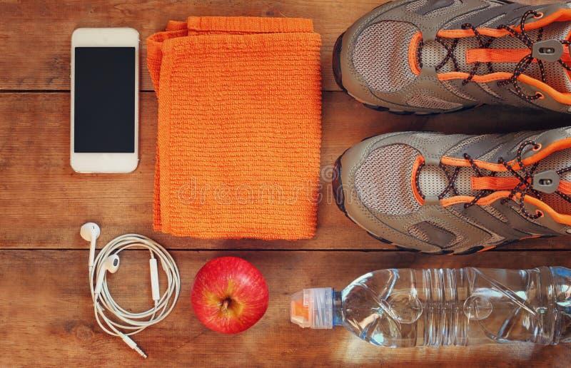 与体育鞋类的健身概念在木背景 顶视图图象 免版税库存图片