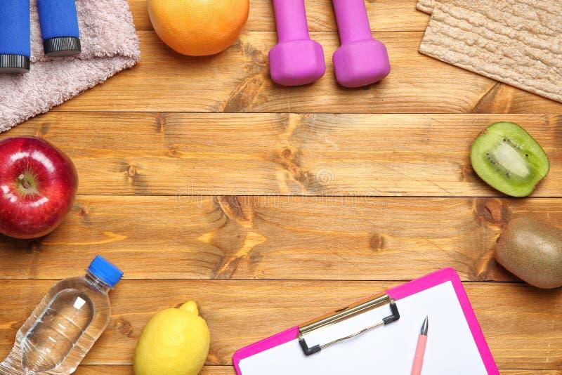 与体育项目、健康食品、剪贴板和空间的平的被放置的构成在木背景的文本的 查出的损失评定躯干重量白人妇女 库存照片