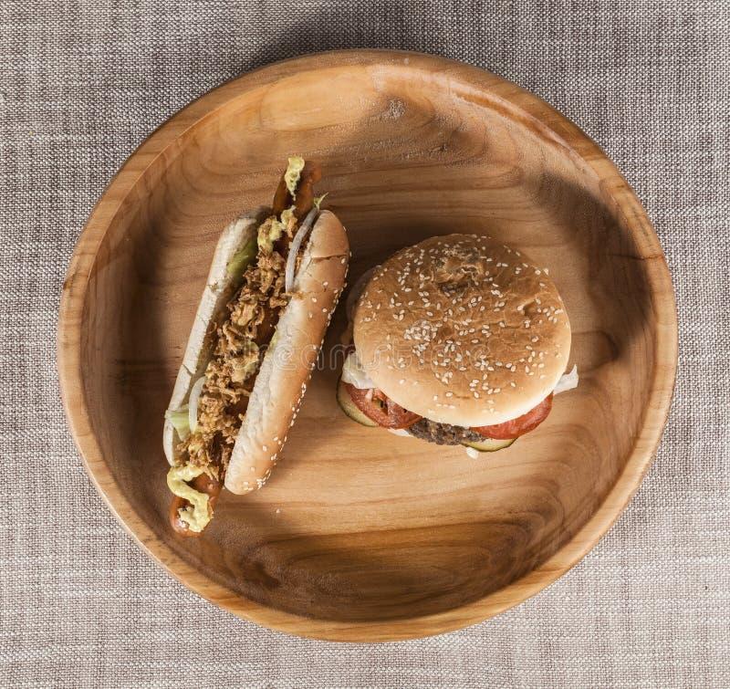 与使有大理石花纹的牛肉和新鲜蔬菜和鲜美热狗剁的新鲜的汉堡包用油煎的葱和新鲜的莴苣与musta 库存图片