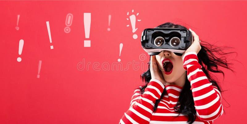 与使用一个虚拟现实耳机的妇女的惊叹号 免版税库存图片