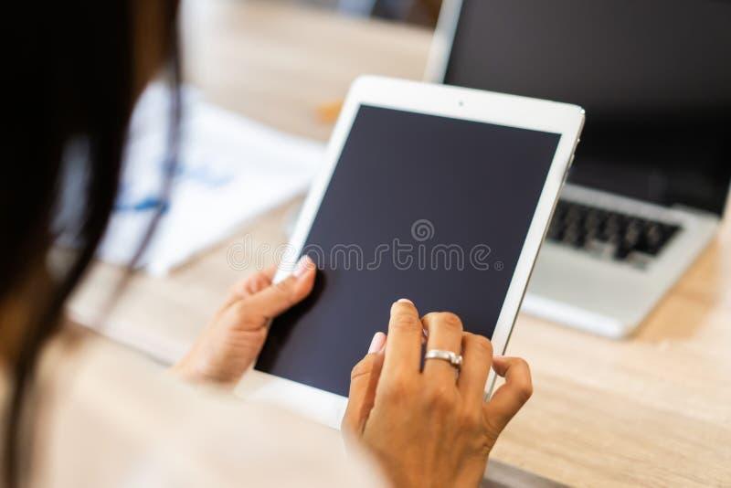 与使用片剂的现代妇女的生活方式或Ipad用拿着触摸屏幕的手 职业妇女的手有巧妙的片剂的 免版税库存图片