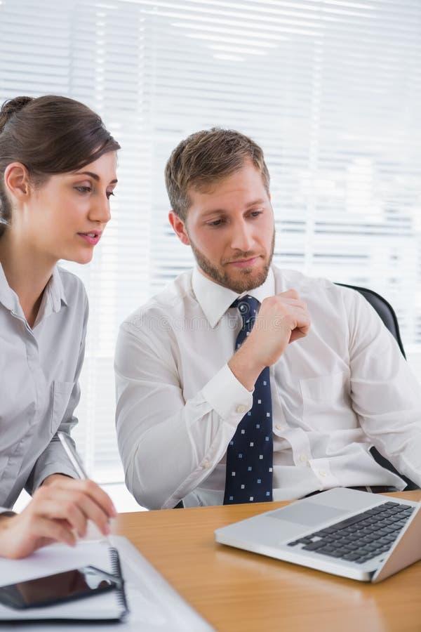 与使用膝上型计算机的同事的商人会谈 免版税库存照片