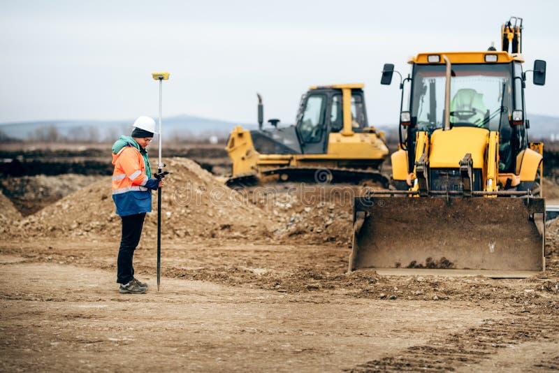 与使用GPS系统和总驻地的测量员的建筑业细节 工程师和测量学 免版税库存照片