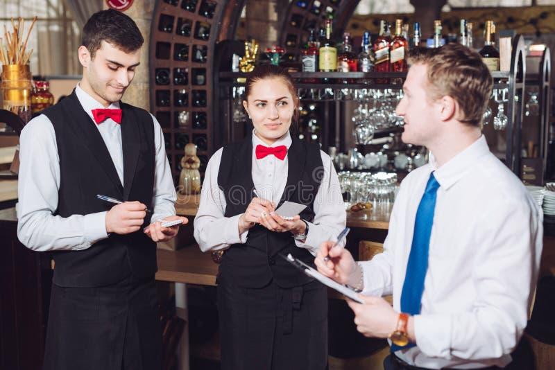 与侍者的经理的简报 餐馆经理和他的职员 库存图片