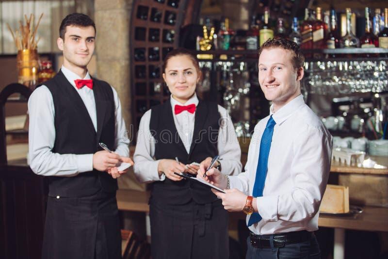 与侍者的经理的简报 餐馆经理和他的职员 免版税库存图片