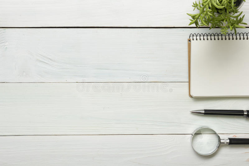 与供应的办公桌桌 顶视图 复制文本的空间 笔记薄,笔,放大镜,花 免版税库存照片