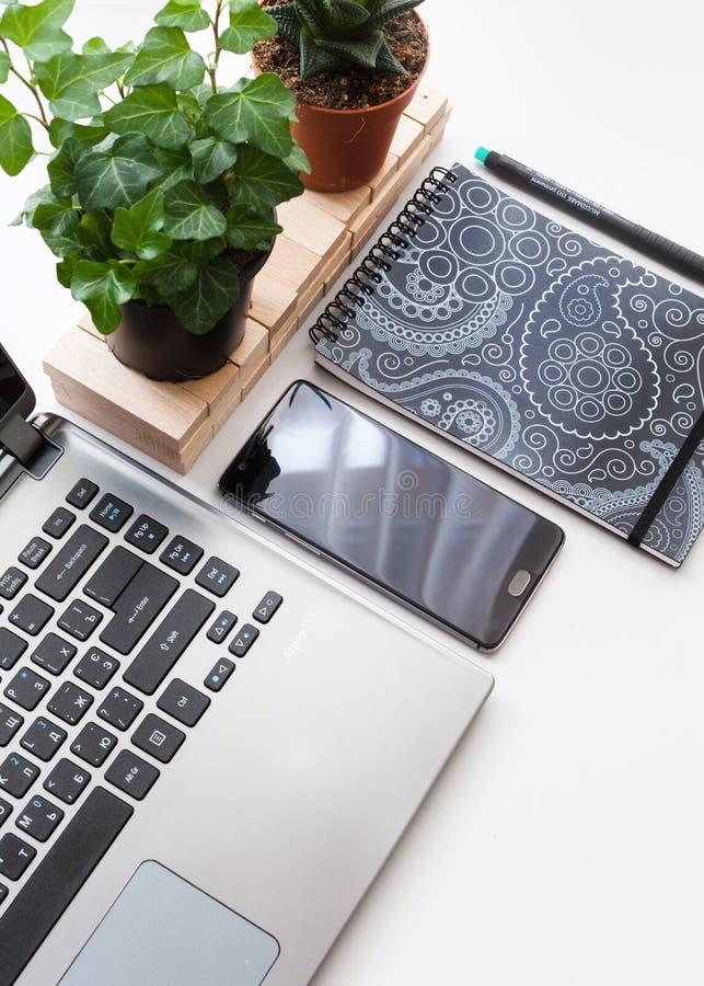 与便携式计算机、智能手机有黑屏幕的和植物的现代白色办公桌桌 与拷贝空间,平的位置的顶视图 免版税库存照片