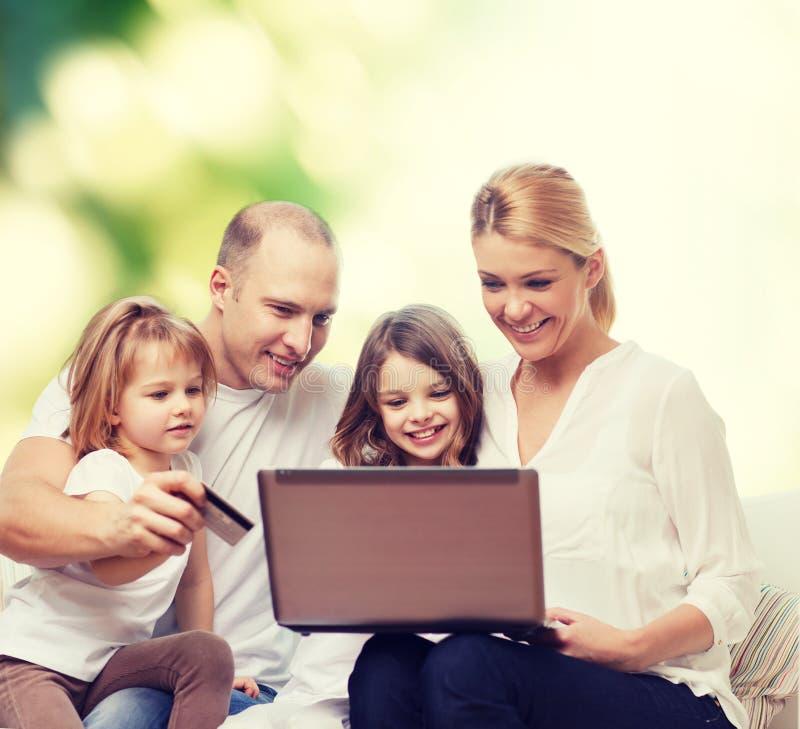 与便携式计算机和信用卡的愉快的家庭 免版税库存照片