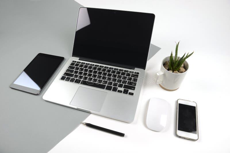 与便携式计算机的办公室桌,笔记本、数字式片剂和智能手机在现代两定调子白色和灰色背景 免版税图库摄影