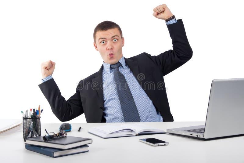 与便携式计算机的微笑的商人和文件在办公室 免版税库存照片