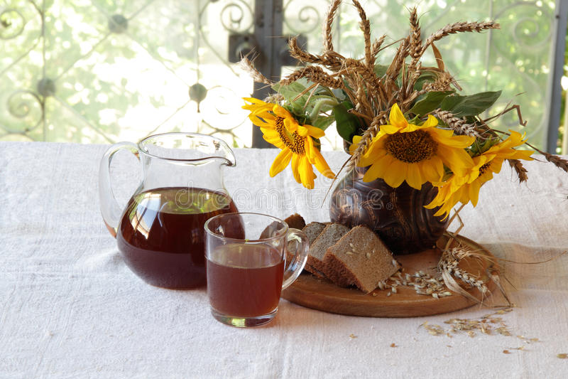 与俄国啤酒(kvas)的静物画在一个透明水罐和花束 库存照片