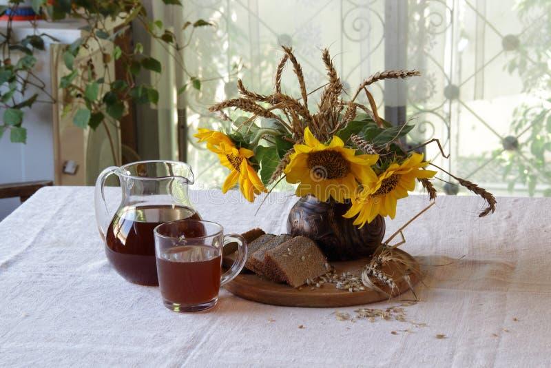 与俄国啤酒(kvas)的静物画在一个透明水罐和花束 免版税库存图片