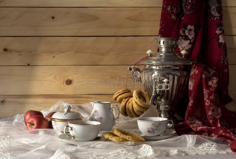 与俄国式茶炊、百吉卷和茶的静物画 免版税库存照片