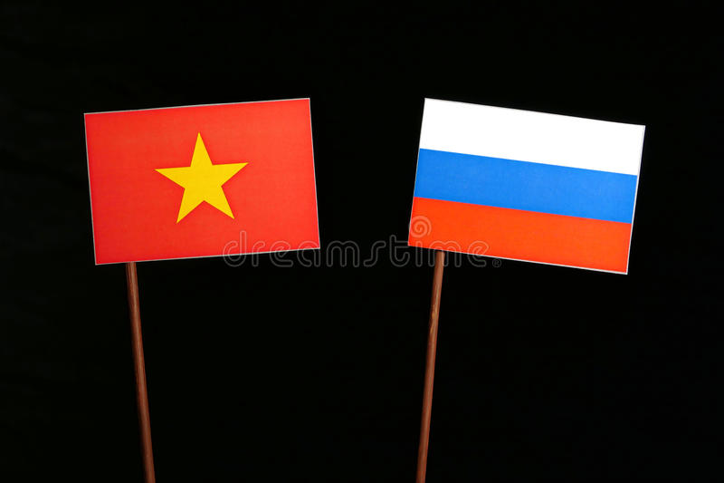 与俄国旗子的越南旗子在黑色 免版税库存图片