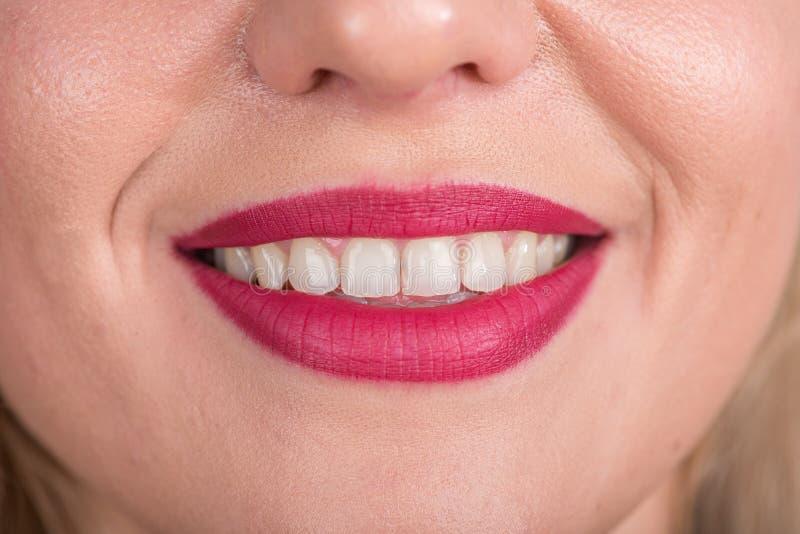 与俏丽的微笑和白色牙的好奇妇女面孔 演播室照片写真 使用明亮的红色唇膏 开放的嘴 免版税图库摄影