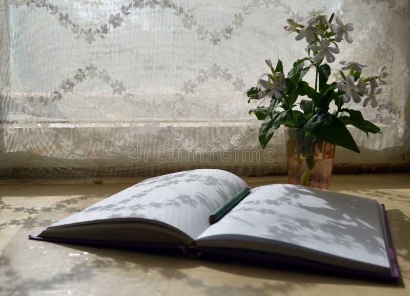 与俏丽的白花和一个开放笔记薄的静物画 库存照片