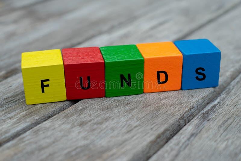 与信件的色的木立方体 词资金被显示,抽象例证 免版税库存照片