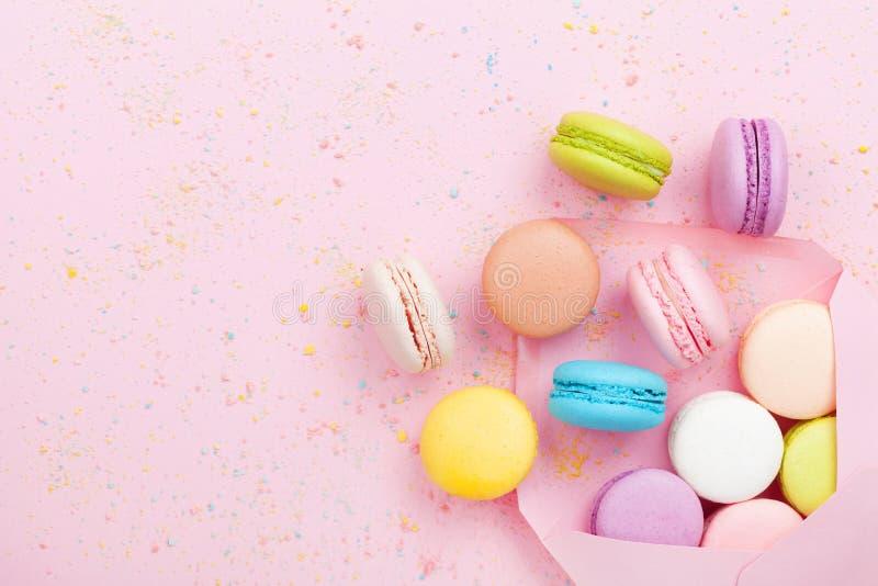 与信封和蛋糕macaron的创造性的在桃红色淡色背景顶视图的构成或蛋白杏仁饼干 平的位置 库存图片