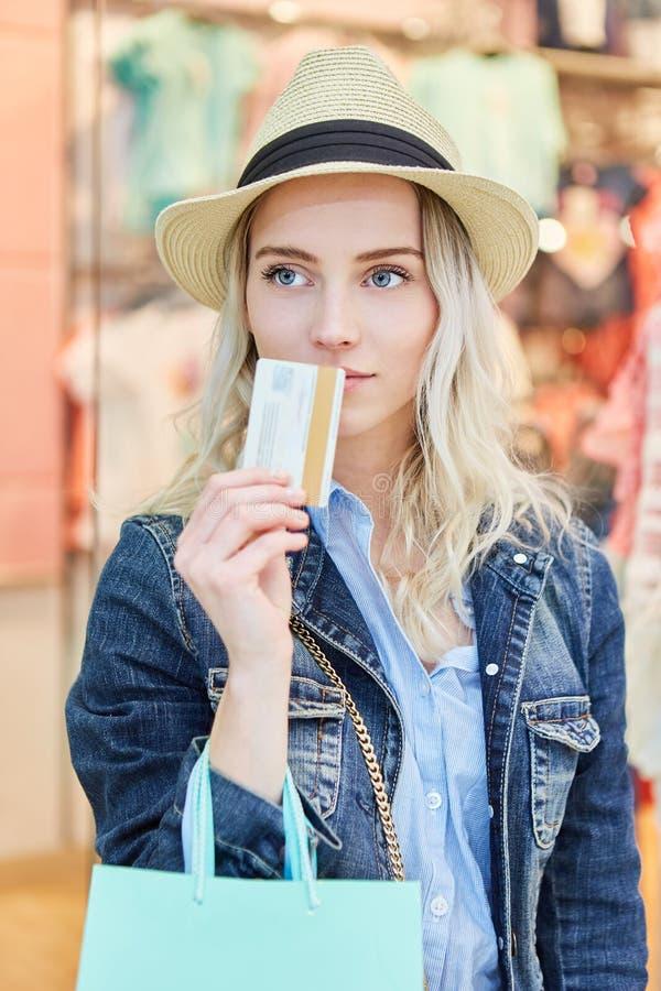 与信用卡的白肤金发的妇女购物 库存照片