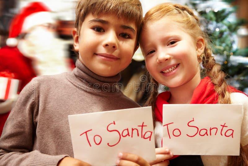 与信件的微笑的孩子给圣诞老人 免版税库存照片