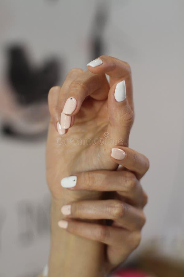 与修指甲的美好的女性现有量 超浅粉红色和经典白色指甲油和井适应了手指 免版税库存图片