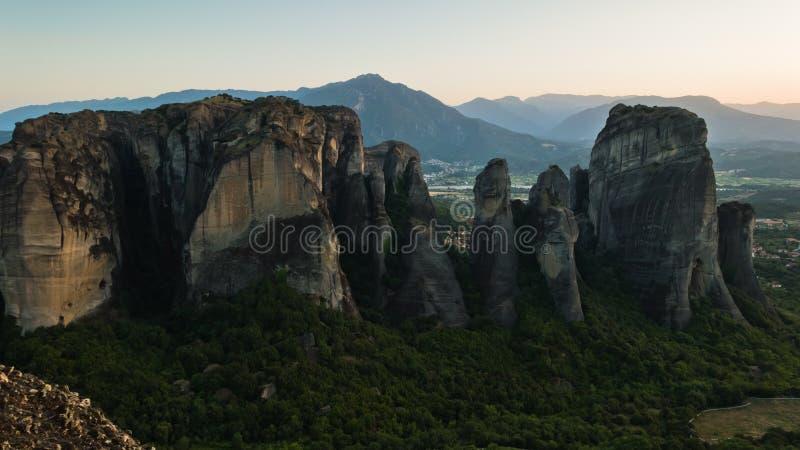 与修道院的巨大的在遥远的山后的岩石和日落在迈泰奥拉,色萨利 免版税库存照片