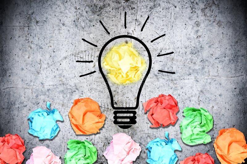 与倍数的激发灵感概念弄皱了围拢一个电灯泡的五颜六色的纸张 库存照片