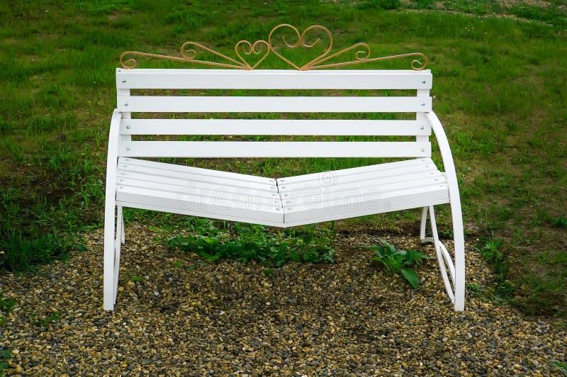 与倾斜的位子的白色长凳和解 免版税库存图片