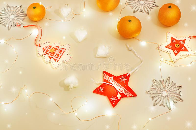 与假日光的圣诞节静物画 蜜桔,木装饰红色星,圣诞树,银色雪花,白色玻璃 库存图片