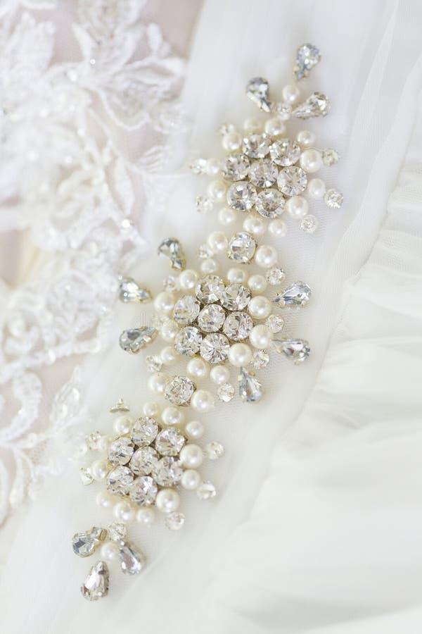 与假钻石和珍珠的装饰首饰在婚礼礼服 库存照片