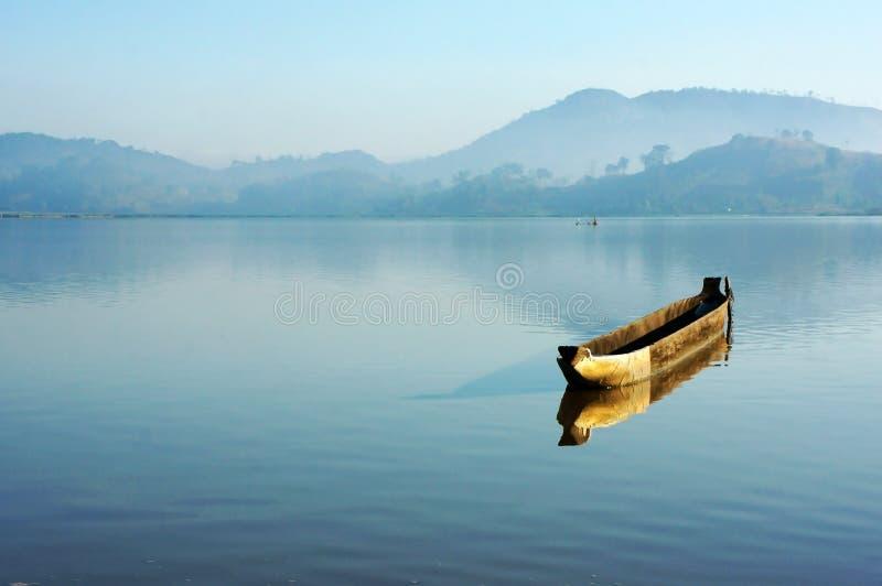 与偏僻的木小船(独木舟)的迷人的风景在l 免版税库存图片