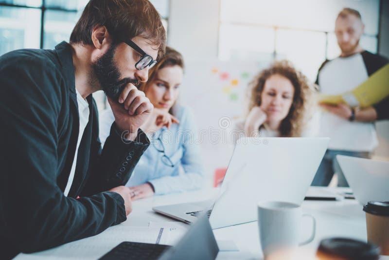 与做交谈的企业队的有胡子的商人在晴朗的会议室 水平 被弄脏的背景 免版税库存照片