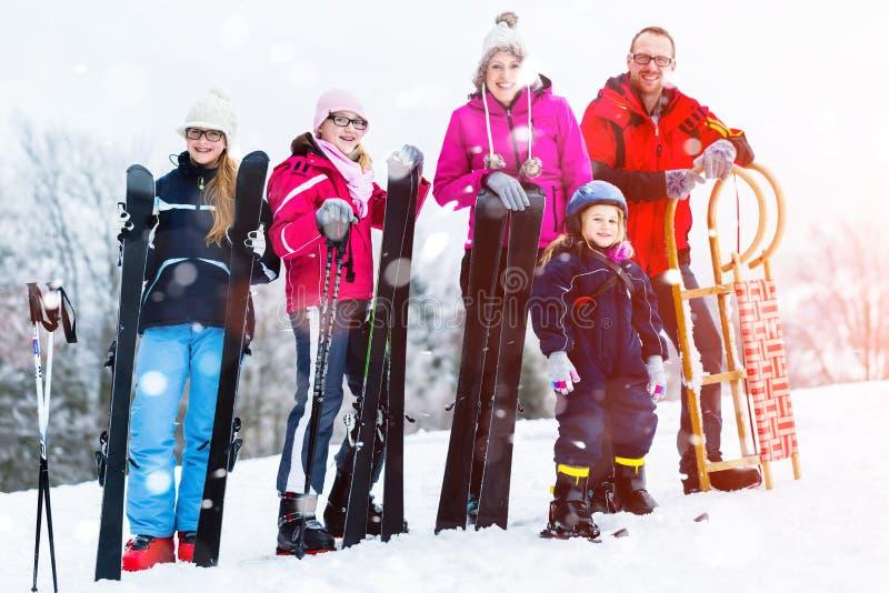 与做冬季体育的雪撬和滑雪的家庭 免版税库存照片