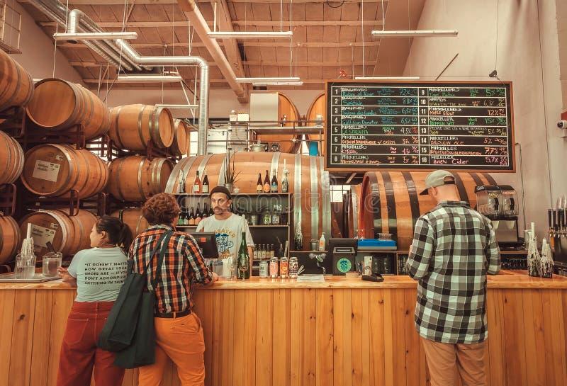 与做出在啤酒之间的饮者和侍酒者的酒吧柜台选择由Mikkeller啤酒厂 免版税库存照片
