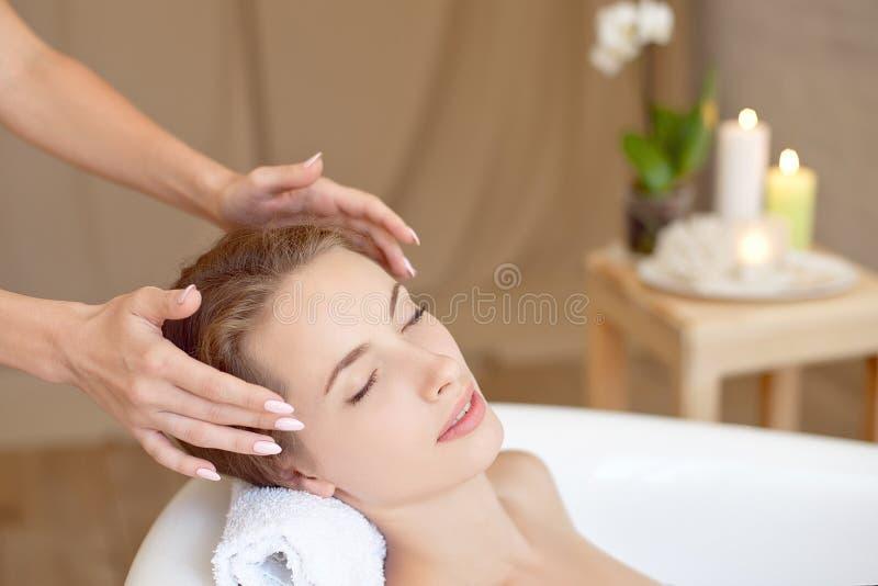 与做在浴缸的完善的皮肤的妇女面孔面部按摩 库存照片