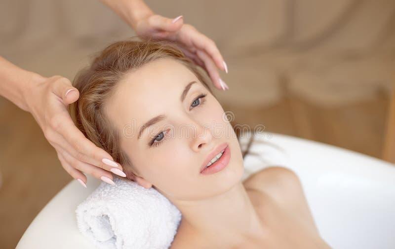 与做在浴缸的完善的皮肤的妇女面孔面部按摩 免版税库存图片