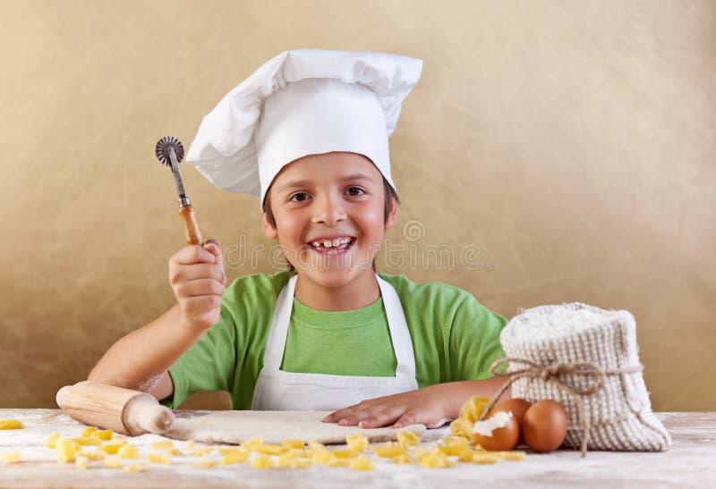 与做面团或曲奇饼的厨师帽子的愉快的孩子 图库摄影