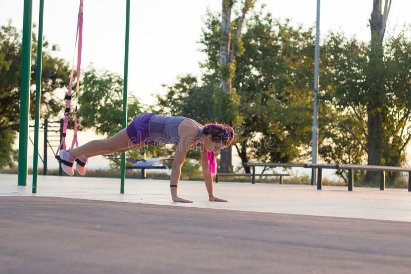 与停止皮带的锻炼在室外健身房,训练及早在公园的早晨,日出背景的适合的妇女 免版税库存照片
