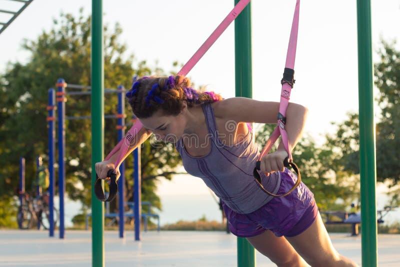 与停止皮带的锻炼在室外健身房,训练及早在公园的早晨,日出背景的适合的妇女 免版税库存图片