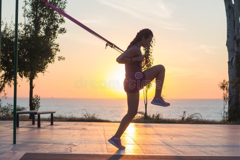 与停止皮带的锻炼在室外健身房,训练及早在公园的早晨,日出背景的适合的妇女 免版税图库摄影
