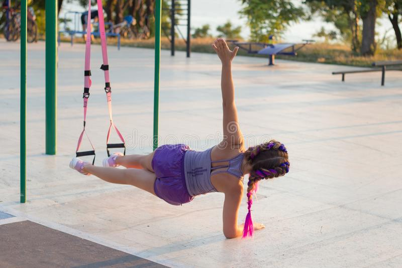 与停止皮带的锻炼在室外健身房,训练及早在公园的早晨,日出背景的适合的妇女 图库摄影
