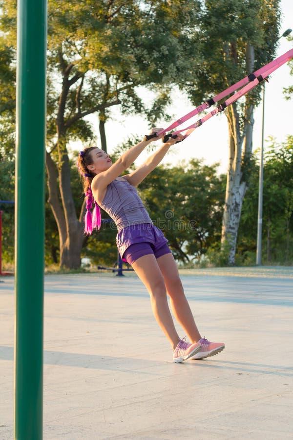 与停止皮带的锻炼在室外健身房,训练及早在公园的早晨,日出背景的适合的妇女 库存照片
