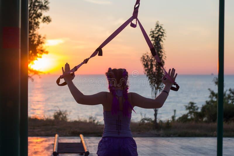 与停止皮带的锻炼在室外健身房,训练及早在公园的早晨,日出背景的适合的妇女 库存图片