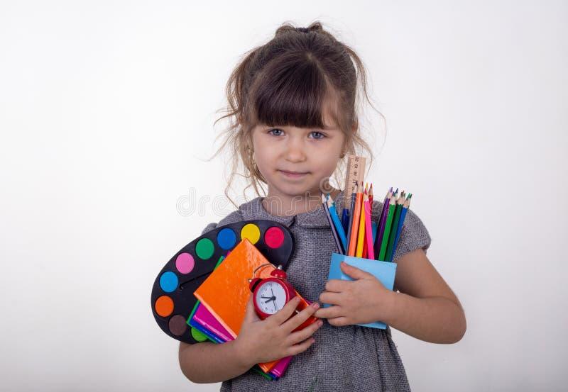 与停留在白色背景的学校用品的愉快的孩子 准备好的学校 免版税库存图片