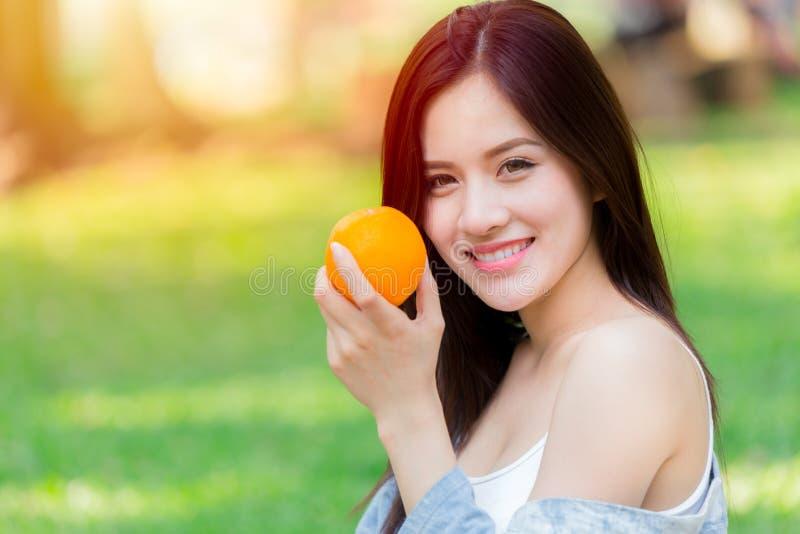与健康亚裔妇女高维生素C的橙色果子 免版税库存图片