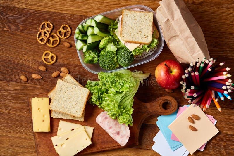 与健康午餐盒的学校午餐断裂和在木书桌,选择聚焦上的学校用品的概念 库存图片